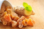 picture of home remedy  - Closeup dried candied crystallized ginger pieces and raw root on wooden table - JPG