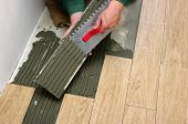 Man installs a ceramic tile