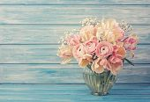Pink ranunculus flowers on a blue wooden background