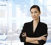 Confident smiling asian businesswoman standing in front of bright business office with arms crossed, looking at camera. Copyspace.