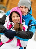 Half-length portrait of hugging couple who wears warm caps and jackets during winter vacations