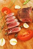 fresh grilled beef meat fillet sliced on wooden board with cutlery isolated  over white background