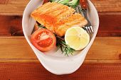 served fish: roast salmon fish over glass plate over wood