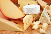 stock photo of deli  - image of cheeses on wooden plate over table - JPG