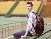 Handsome Young Pensive Man With Backpack, Modern Hipster Sitting On A Bench