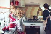 picture of little kids  - Mother with her 5 years old kids cooking holiday pie in the kitchen - JPG