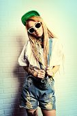 Modern teenage girl with blonde dreadlocks standing by the brick wall. Jeans style. Modern generation.