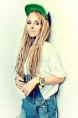 image of dreadlocks  - Modern teenage girl with blonde dreadlocks standing by the brick wall - JPG