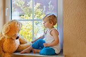Lovely Child Of Two Years Sitting Near Window With Big Toy Bear.