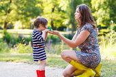 Mother And Little Adorable Toddler Daughter In Yellow Rubber Boots
