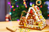 picture of gingerbread house  - Gingerbread house with Christmas tree and lights on background - JPG