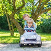 Two Happy Twin Boys Playing With Toy Car