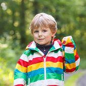 Portrait Of Blond Little Preschool  Boy In Colorful Waterproof Raincoat In Autumn Forest