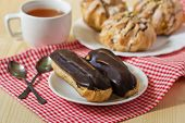 Tasty Eclairs On Table With Tea Cup