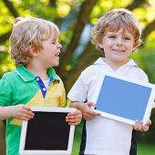 Two Happy Little Sibling Kids Holding Tablet Pc, Outdoors