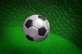 Goal. Soccer ball in goal net with green field background