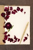 Old fashioned vintage hemp notebook, ink pen and red rose with petals over lokta paper background.