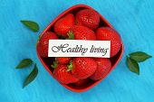 Healthy living card with bowl full of fresh strawberries