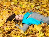Beautiful lady wearing blue scarf lying in dry leaves