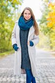 Pretty Smiling Woman in Cozy Autumn Outfit Style Posing at the Pathway. Captured Outdoor. Looking at