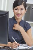 Portrait of a beautiful young Asian Chinese woman or businesswoman at the computer in her office writing in her diary