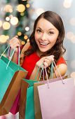 sale, gifts, holidays and people concept - smiling woman with colorful shopping bags over living roo