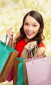 sale, gifts, christmas, holidays and people concept - smiling woman with colorful shopping bags over