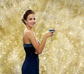party, drinks, holidays, luxury and celebration concept - smiling woman in evening dress holding coc