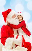 holidays, christmas, childhood and people concept - smiling little girl hugging with santa claus ove