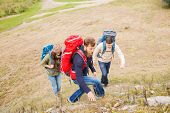 adventure, travel, tourism, hike and people concept - group of smiling friends with backpacks climbing on hill