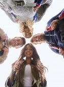 adventure, travel, tourism, hike and people concept - group of smiling friends with backpacks standing in circle outdoors