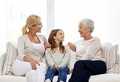 family, happiness, generation and people concept - smiling mother, daughter and grandmother sitting