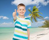 childhood, summer vacation, travel, gesture and people concept - smiling little boy showing thumbs up over tropical beach background