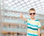 happiness, summer, childhood, gesture and people concept - smiling boy in sunglasses over shopping center background showing thumbs up