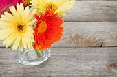 Colorful gerbera flowers on wooden table with copy space