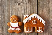 Christmas homemade gingerbread girl and house on wooden table