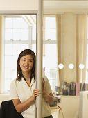 Asian businesswoman standing doorway