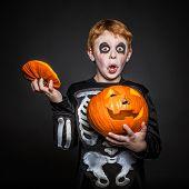 Surprised red hair kid in Halloween costume holding a orange pumpkin. Skeleton
