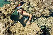 Man In The Mask Floats On A Coral Reef In The  Sea