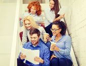 business, office and startup concept - smiling creative team with papers and take away coffee on staircase