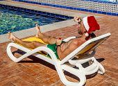 A Man In A Santa's Hat Blows Soap Bubbles On The Tropical Resort Pool