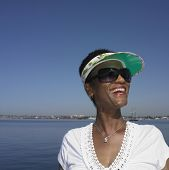 Senior African woman smiling next to water