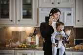 Hispanic mother on cell phone with baby in front pack