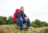 adventure, travel, tourism, hike and people concept - smiling man with red backpack sitting on ground