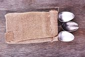 Tableware wrapped in sackcloth napkin on wooden background