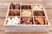 Wooden box with set of coffee and cocoa beans, sugar cubes, dark chocolate, cinnamon and anise over