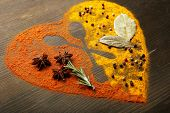 Spices on table in shape of heart with spoon silhouette, close-up