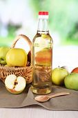 Apple cider vinegar in glass bottle and ripe fresh apples, on wooden table, on nature background