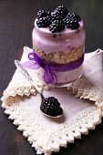 Healthy breakfast - yogurt with  blackberries and muesli served in glass jar, on dark wooden background