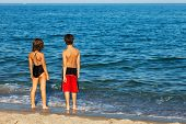 brother and sister stand in front of the sea